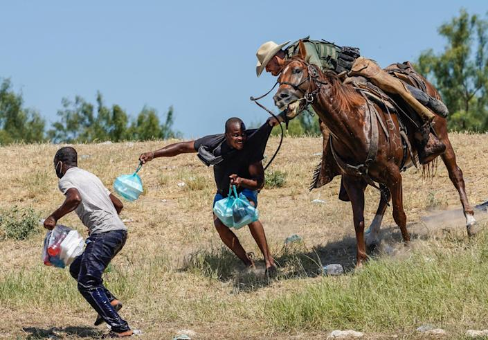 A U.S. Customs and Border Patrol agent on horseback tries to stop a Haitian migrant from entering an encampment on the banks of the Rio Grande in Del Rio, Texas, on Sept. 19, 2021.