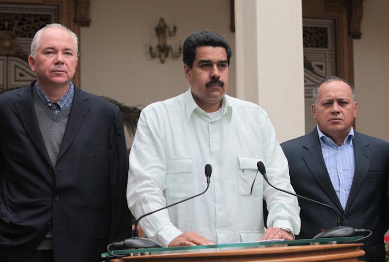 """In this photo released by Miraflores Press Office, Venezuela's Vice President Nicolas Maduro, center, addresses the nation on live television flanked by Oil Minister Rafael Ramirez, left, and National Assembly President Diosdado Cabello at the Miraflores presidential palace in Caracas, Venezuela, Wednesday, Dec. 12, 2012.  Maduro said that Venezuela's President Hugo Chavez will face a """"complex and hard"""" process after undergoing his fourth cancer-related operation in Cuba on Tuesday. Over the weekend, Chavez named Maduro as his chosen political heir. (AP Photo/Miraflores Press Office, Efrain Gonzalez)"""