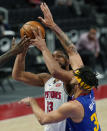 Detroit Pistons center Jahlil Okafor (13) is fouled by Denver Nuggets center JaVale McGee (34) during the second half of an NBA basketball game, Friday, May 14, 2021, in Detroit. (AP Photo/Carlos Osorio)