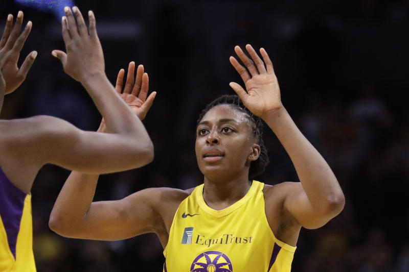 """FILE - In this Friday, May 31, 2019, file photo, Los Angeles Sparks' Chiney Ogwumike (13), obscured at left, and her sister Nneka Ogwumike celebrate after a win over the Connecticut Sun in a WNBA basketball game in Los Angeles. The WNBA and its union announced a tentative eight-year labor deal Tuesday, Jan. 14, 2020,  that will allow top players to earn more than $500,000 while the average annual compensation for players will surpass six figures for the first time. """"It was collaborative effort,'"""" WNBA players' union president Nneka Ogwumike said.  (AP Photo/Marcio Jose Sanchez, File)"""