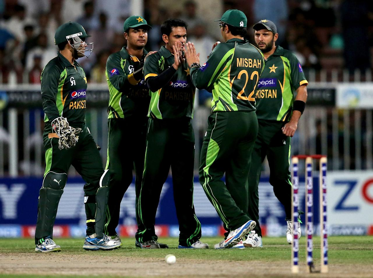 SHARJAH, UNITED ARAB EMIRATES - DECEMBER 18: Players of Pakistan celebrate  during the first One-Day International (ODI ) match between Sri Lanka and Pakistan at the Sharjah Cricket Stadium on December 18, 2013 in Sharjah, United Arab Emirates.  (Photo by Francois Nel/Getty Images)