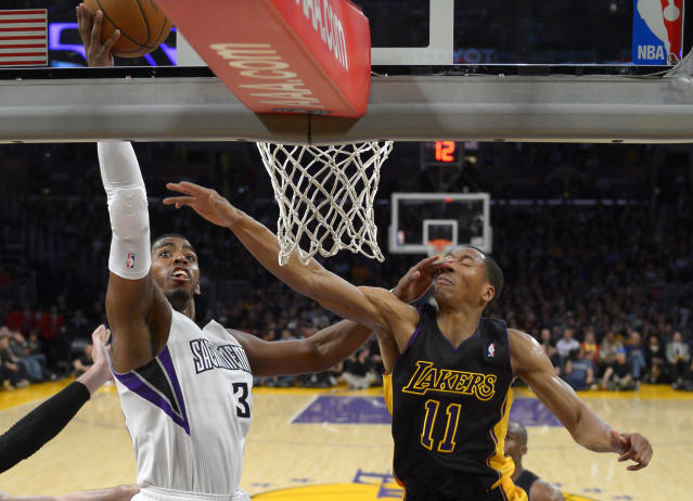 Sacramento Kings forward Jason Thompson, left, shoots as Los Angeles Lakers forward Wesley Johnson is hit in the face during the first half of an NBA basketball game on Friday, Feb. 28, 2014, in Los Angeles. (AP Photo/Mark J. Terrill)