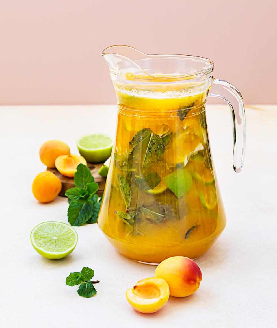 Apricot cocktail or ice tea with fresh mint, lime and apricots. Summer refreshing cold drink. Light concrete background.