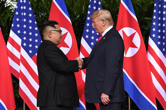 <p>North Korea's leader Kim Jong Un (L) shakes hands with US President Donald Trump (R) at the start of their historic US-North Korea summit, at the Capella Hotel on Sentosa island in Singapore on June 12, 2018. – Donald Trump and Kim Jong Un have become on June 12 the first sitting US and North Korean leaders to meet, shake hands and negotiate to end a decades-old nuclear stand-off. (Photo: Saul Loeb/AFP/Getty Images) </p>