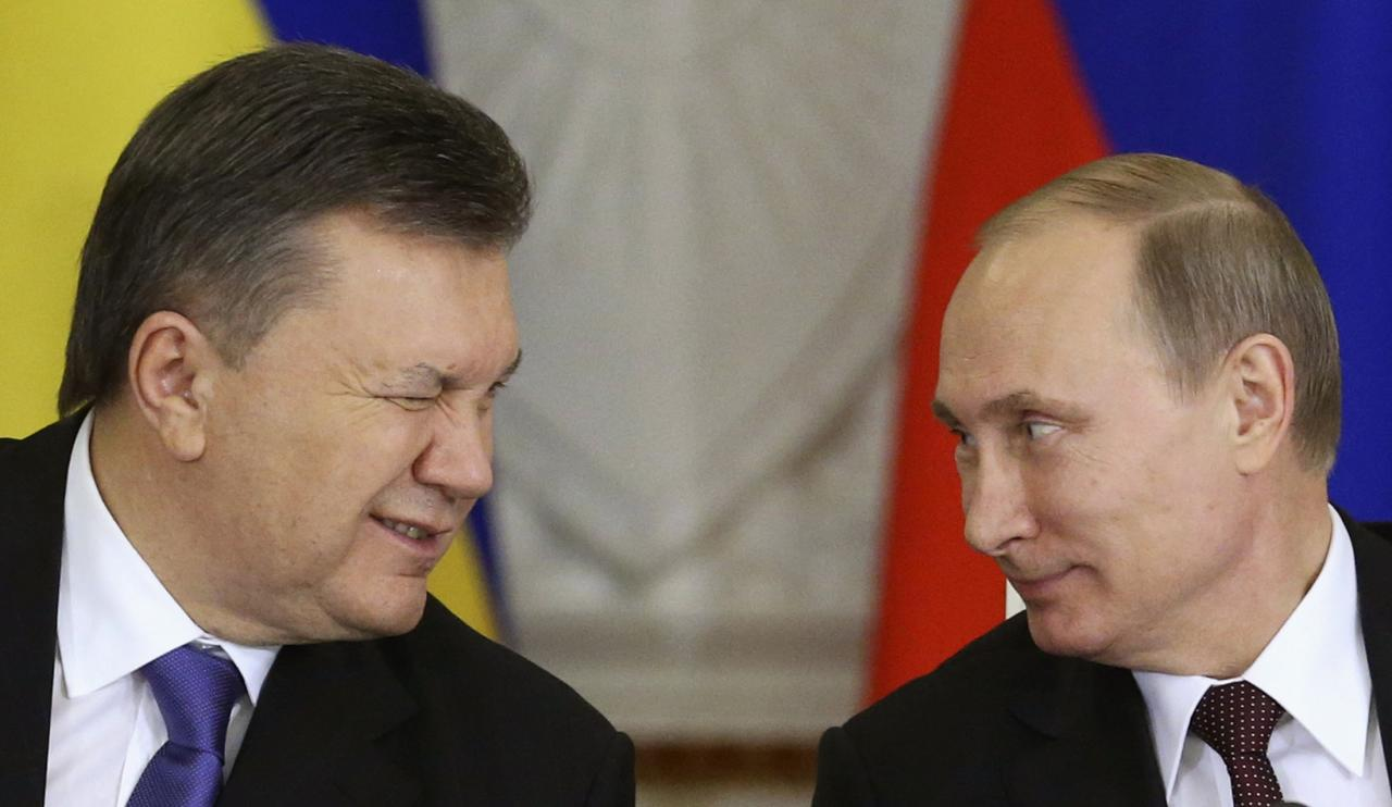 Ukrainian President Viktor Yanukovich (L) gives a wink to his Russian counterpart Vladimir Putin during a signing ceremony after a meeting of the Russian-Ukrainian Interstate Commission at the Kremlin in Moscow, December 17, 2013. Russia is planning to buy $15 billion worth of Ukraine's upcoming eurobonds using money from a sovereign wealth fund this year and next, Russian Finance Minister Anton Siluanov said on Tuesday. REUTERS/Sergei Karpukhin (RUSSIA - Tags: BUSINESS POLITICS TPX IMAGES OF THE DAY)