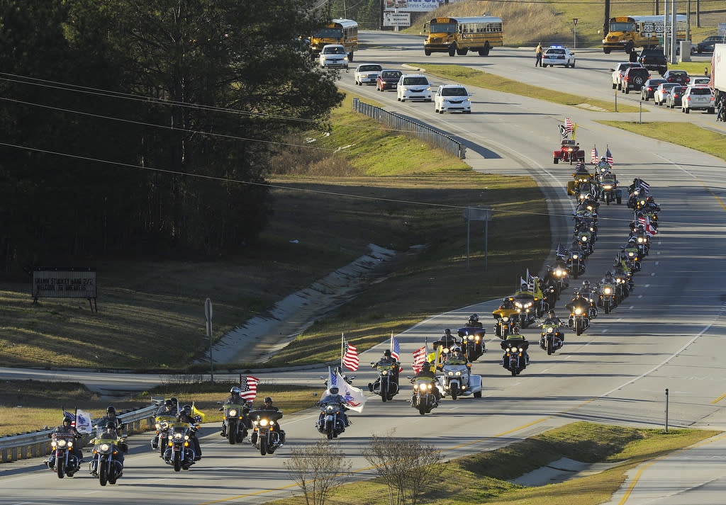 "The funeral procession of slain bus driver Charles ""Chuck"" Poland makes its way down Highway 231 in Ozark, Ala., Sunday Over 60 motorcycles and dozens of school buses join the funeral procession. The Ozark Civic Center was packed with mourners for the funeral. Burial for Poland is in Newton, Ala. (AP Photo/AL.com, Joe Songer)"
