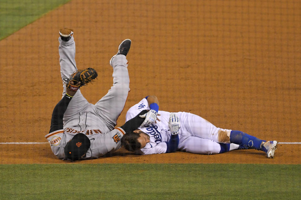 San Francisco Giants third baseman Pablo Sandoval, left, and Los Angeles Dodgers' Chris Taylor fall to the ground after they collided while Taylor was running to first on a single during the fifth inning of a baseball game Friday, July 24, 2020, in Los Angeles. (AP Photo/Mark J. Terrill)