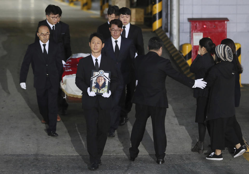 Relatives and friends of late mountain climber Im Il-jin carry his portrait and a casket containing his body from a cargo terminal at Incheon International Airport in Incheon, South Korea, Wednesday, Oct. 17, 2018. Relatives dressed in black funeral suits wept in grief on Wednesday as the bodies of five South Korean mountain climbers arrived home from Nepal where they had died in a storm last week. (Lee Ji-eun/Yonhap via AP)