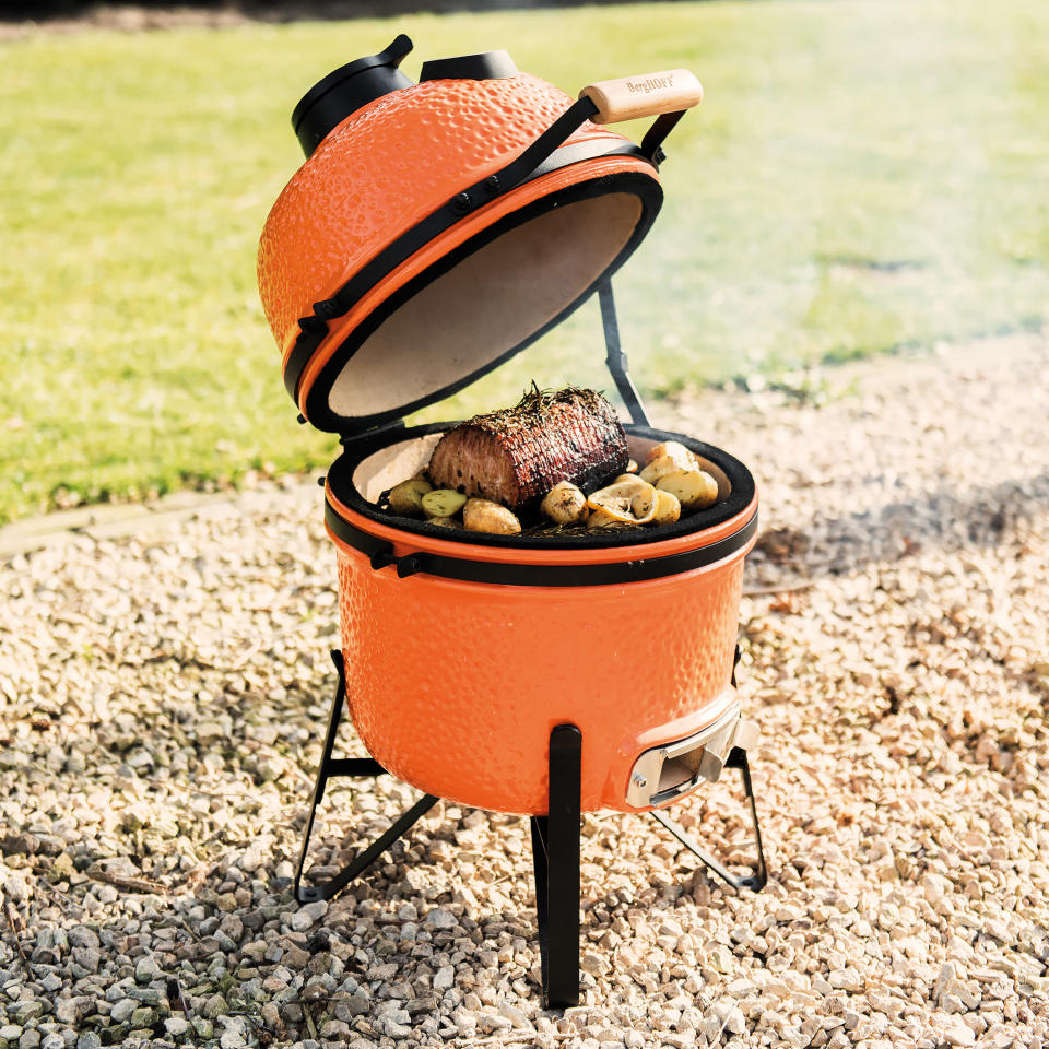 This photo provided by Riverbend Home shows the BergHOFF Small Ceramic BBQ Grill. This wood or charcoal grill is a good smaller size for urban patios, and can be used for searing, roasting, grilling or low-temperature smoking. The ceramic exterior is another grill offered in on-trend orange, as well as dark grey. (BergHOFF/Riverbend Home via AP)