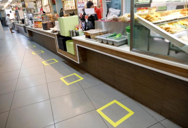 Taped-off areas for customers to distance themselves from each other are seen at a food court due to the outbreak of the coronavirus disease (COVID-19), in Singapore