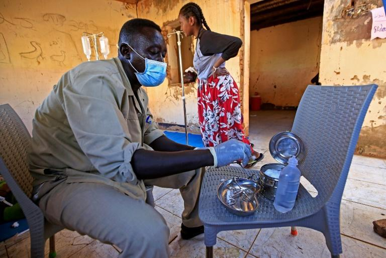 A medic disinfects tools at a medical facility in Um Raquba, a camp that has been set up for Ethiopian refugees in eastern Sudan