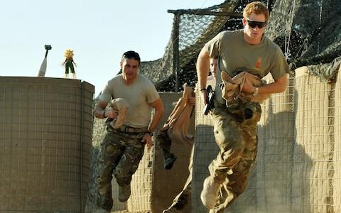 Prince Harry races out from the VHR (very high ready-ness) tent to scramble his Apache  - Credit: AP