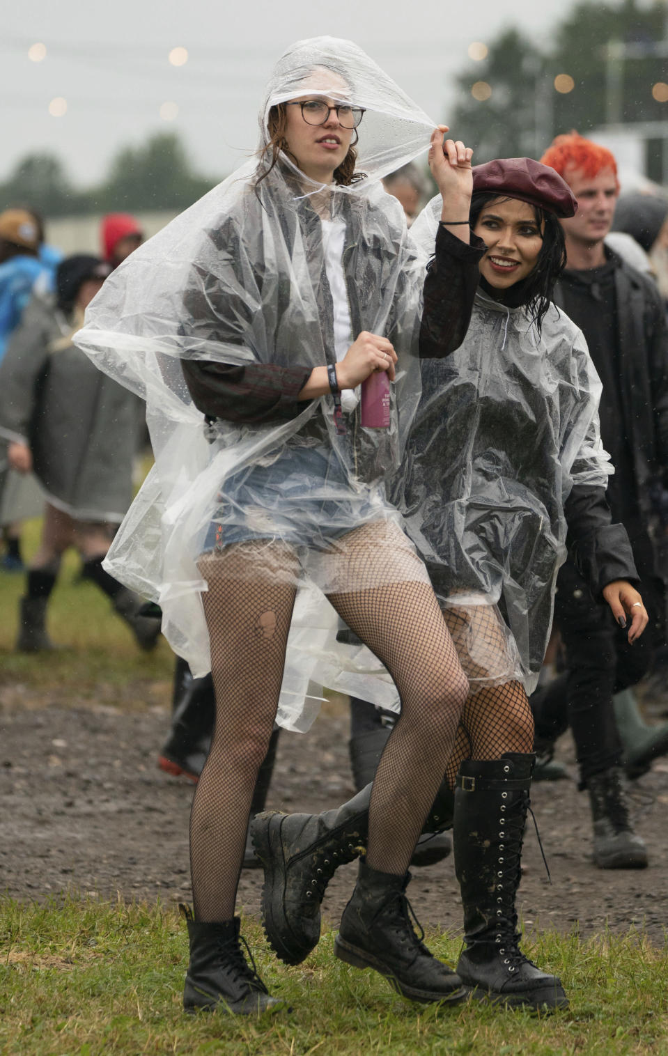 Festivalgoers shelters from the pouring rain on the first day of Download Festival at Donington Park at Castle Donington, England, Friday June 18, 2021. The three-day music and arts festival is being held as a test event to examine how Covid-19 transmission takes place in crowds, with the the capacity significantly reduced from the normal numbers. (Joe Giddens/PA via AP)
