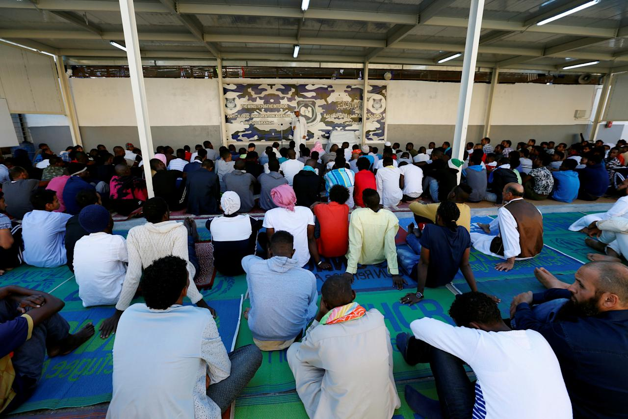 Muslim migrants attend Eid al-Fitr prayers to mark the end of the holy fasting month of Ramadan at a detention centre in Tripoli, Libya June 15, 2018. REUTERS/Ismail Zitouny