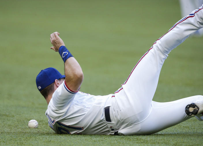 Texas Rangers left fielder David Dahl is unable to catch a hit by San Diego Padres' Jurickson Profar during the first inning of a baseball game, Saturday, April 10, 2021, in Arlington, Texas. (AP Photo/Brandon Wade)
