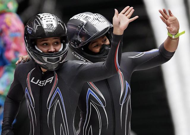 The team from the United States USA-3, piloted by Jazmine Fenlator with brakeman Lolo Jones, left, wave to fans after their final run during the women's bobsled competition at the 2014 Winter Olympics, Wednesday, Feb. 19, 2014, in Krasnaya Polyana, Russia. (AP Photo/Michael Sohn)