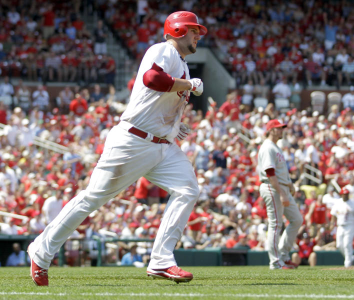 St. Louis Cardinals' Matt Adams, left, rounds the bases after hitting a solo home run off Philadelphia Phillies pitcher Chad Qualls, right, during the sixth inning of a baseball game, Sunday, May 27, 2012, in St. Louis. (AP Photo/Jeff Roberson)