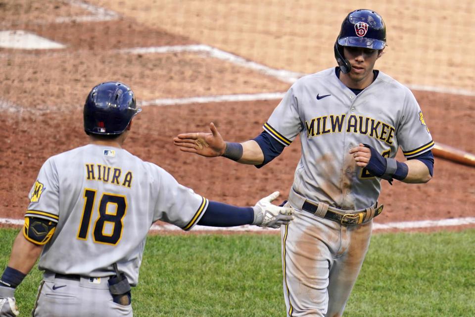 Milwaukee Brewers' Christian Yelich, right, celebrates with Keston Hiura after scoring on a single by Milwaukee Brewers' Jace Peterson during the sixth inning of a baseball game against the Pittsburgh Pirates in Pittsburgh, Saturday, July 3, 2021. (AP Photo/Gene J. Puskar)