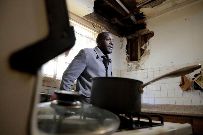 FILE- In this Nov. 8, 2018 file photo, a hole is seen on the wall and ceiling in Desmond Odom's kitchen as he talks to The Associated Press about the lead in his tap water in Newark, N.J. A water leak forced Odom to hire a contractor and pay $2,000 to replace a lead pipe that burst, but he claims he and his family have stopped drinking the tap water because of the lead pipes in his home. New Jersey's biggest city has recently been the epicenter of a problem with lead in drinking water, but the United States has an estimated 6 million lead pipes, many of them in unknown locations. (AP Photo/Julio Cortez, File)