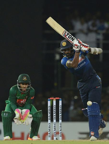 Sri Lankan cricketer Chamara Kapugedera (R) is watched by Bangladesh wicketkeeper Mushfiqur Rahim as he plays a shot during their second T20 match in Colombo on April 6, 2017