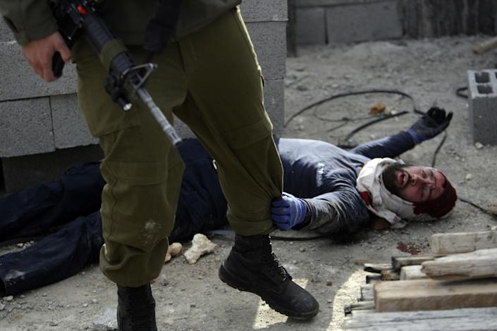 """An injured Israeli settler grabs an Israeli soldier's leg to get his attention after the settler was detained by Palestinian villagers in a building under construction near the West Bank village of Qusra, southeast of the city of Nablus, Tuesday, Jan. 7, 2014. Palestinians held more than a dozen Israeli settlers for about two hours Tuesday in retaliation for the latest in a string of settler attacks on villages in the area, witnesses said. The military said the chain of events apparently began after Israeli authorities removed an illegally built structure in Esh Kodesh, a rogue Israeli settlement in the area. In recent years, militant settlers have often responded to any attempts by the Israeli military to remove parts of dozens of rogue settlements, or outposts, by attacking Palestinians and their property. The tactic, begun in 2008, is known as """"price tag."""" (AP Photo/Nasser Ishtayeh)"""