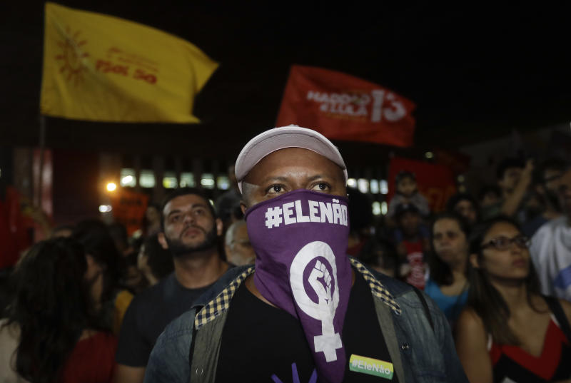 "A man wears a scarf that reads in Portuguese ""Not him"", during a protest against Jair Bolsonaro, a far-right presidential candidate in Sao Paulo, Brazil, Wednesday, Oct. 10, 2018. Bolsonaro will face off with Workers Party candidate Fernando Haddad in an election runoff on Oct. 28. (AP Photo/Andre Penner)"