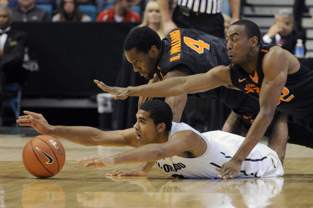 Colorado's Xavier Talton is covered by Oklahoma State's Brian Williams (4) and Markel Brown as they reach for a loose ball during the first half of an NCAA college basketball game on Saturday, Dec. 21, 2013, in Las Vegas. (AP Photo/David Becker)