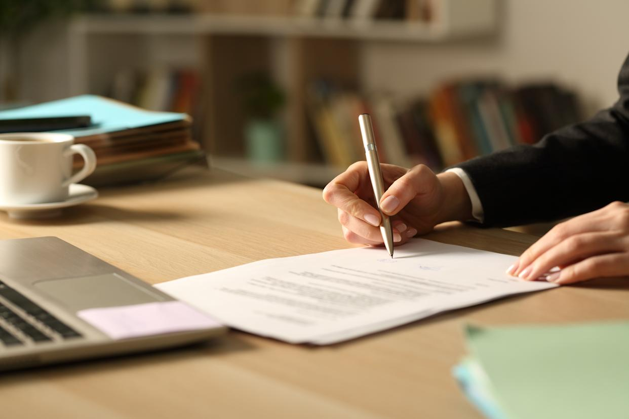 Entrepreneur hands signing contract in the night at home