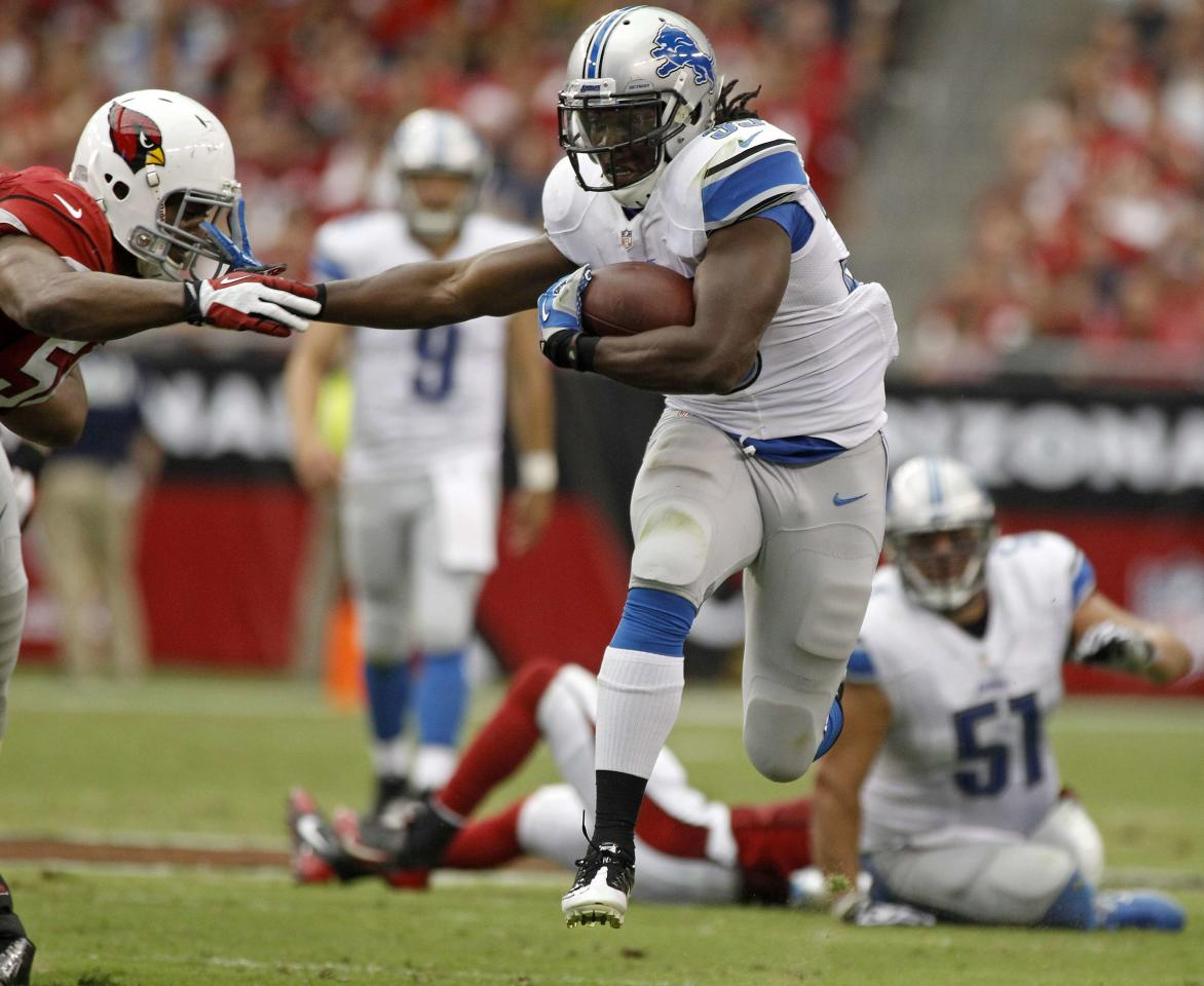 Detroit Lions running back Joique Bell (R) stiff arms Arizona Cardinals linebacker Karlos Dansby on a first down run during the second quarter of their NFL football game in Phoenix, Arizona, September 15, 2013. REUTERS/Ralph D. Freso (UNITED STATES - Tags: SPORT FOOTBALL)