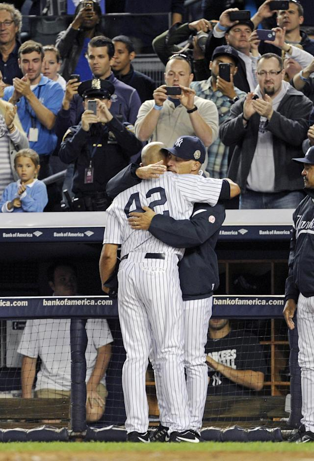 New York Yankees manager Joe Girardi hugs pitcher Mariano Rivera (42) during the ninth inning of a baseball game against the Tampa Bay Rays on Thursday, Sept. 26, 2013, at Yankee Stadium in New York. Rivera was playing in his final home game before retiring. The Yankees won 4-0. (AP Photo/Bill Kostroun)