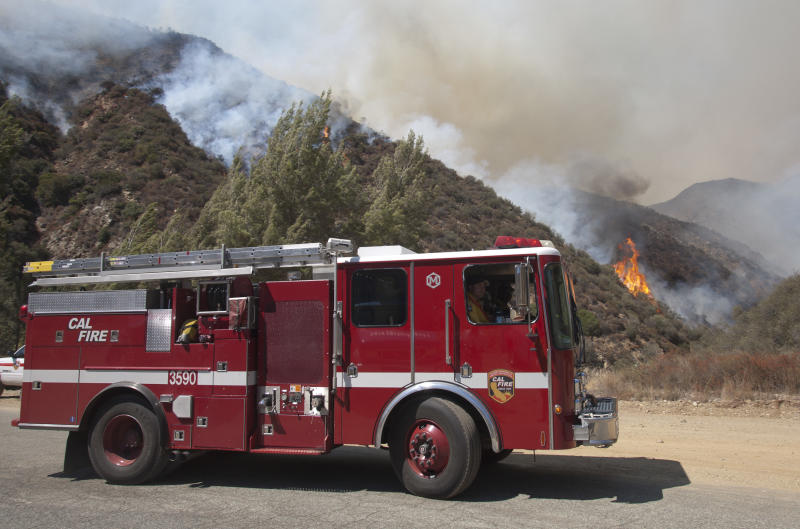 A fire engine pulls away as firefighters fight a wildfire in the Angeles National Forest north of Glendora, Calif. Monday, Sept. 3, 2012. A day after the wildfire broke out near a campground and forced the evacuation of thousands of campers and picnickers it had grown to more than 4,100 acres, or roughly 6 square miles, and was just five percent contained. (AP Photo/Jason Redmond)