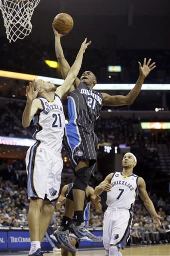 Orlando Magic's Moe Harkless, center goes to the basket over Memphis Grizzlies' Tayshaun Prince, left, and Jerryd Bayless (7) during the first half of an NBA basketball game in Memphis, Tenn., Friday, Feb. 22, 2013. (AP Photo/Danny Johnston)