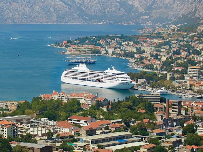 A large cruise ship, the Seven Seas Mariner docks in the seaside city of Kotor, Montenegro