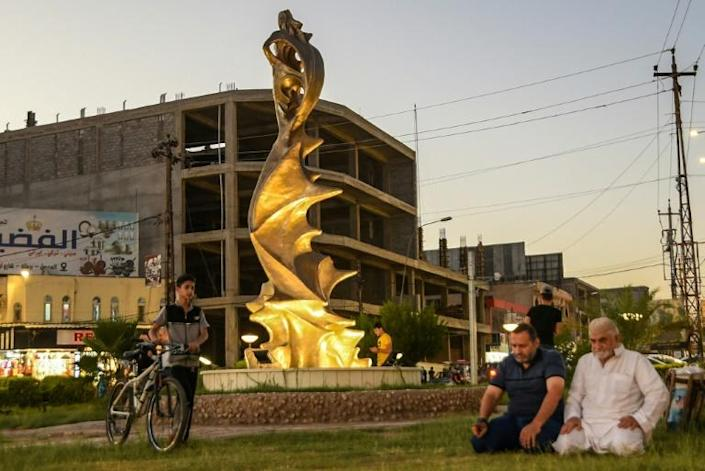 Men pray near the statue of 'My Lovely Lady' erected in the centre of a square in Iraq's northern city of Mosul