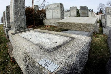 A headstone, one of many, lays on the ground after vandals pushed them off their bases in the Mount Carmel Cemetery, a Jewish cemetery, in Philadelphia, Pennsylvania, U.S. February 27, 2017. REUTERS/Tom Mihalek