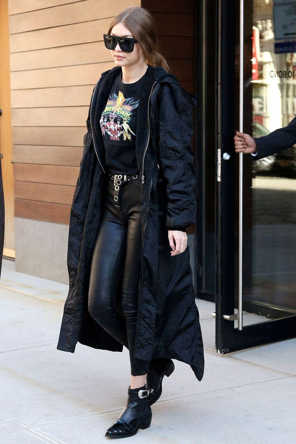 <p>In a Power Rangers t-shirt under a black hooded sweatshirt and long windbreaker jacket with Paige leather pants, Tommy Hilfiger ankle boots and Quay oversized sunglasses while out in New York City. </p>