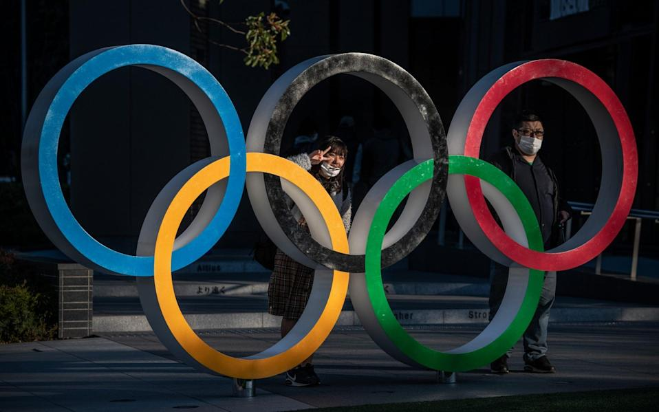 People wearing face masks pose for photographs next to Olympic Rings  - Getty Images