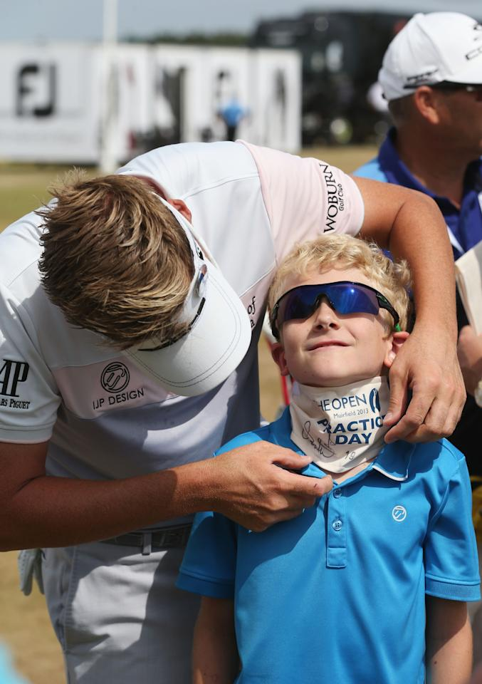 GULLANE, SCOTLAND - JULY 17: Ian Poulter of England with son Luke on the driving range ahead of the 142nd Open Championship at Muirfield on July 17, 2013 in Gullane, Scotland. (Photo by Andrew Redington/Getty Images)