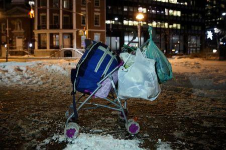 A homeless man's cart rests on the sidewalk as New York City's Coalition for the Homeless delivers food, donated clothing and supplies to homeless people as part of their weekly distribution during winter storm Grayson in Manhattan, New York City, U.S., January 4, 2018. REUTERS/Amr Alfiky