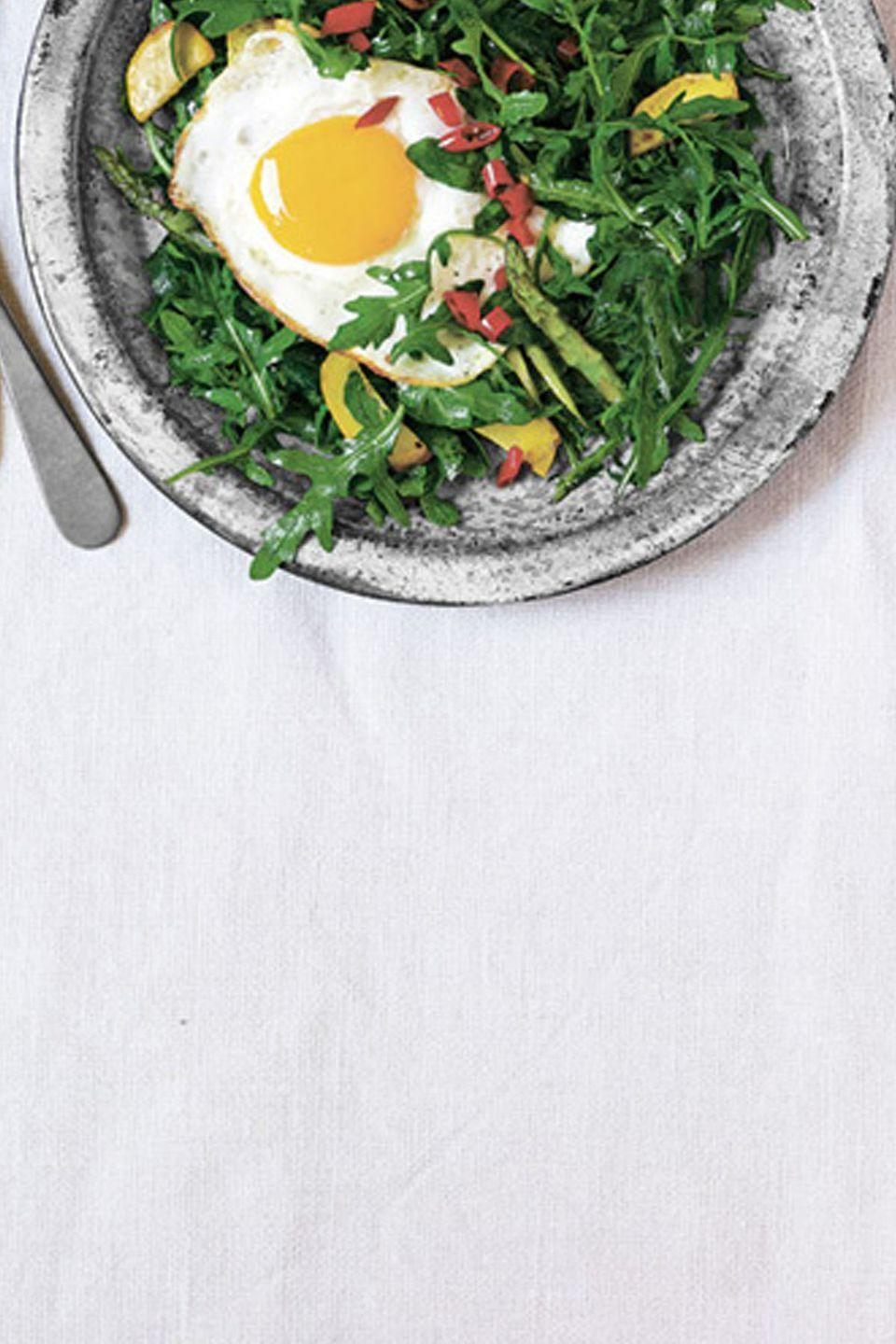 "<p>This vibrant mix of vegetables - topped with hot pickled peppers and a hearty egg - proves a well-rounded option for brunch or dinner. <br></p><p><a href=""https://www.womansday.com/food-recipes/food-drinks/recipes/a38030/wild-arugula-summer-squah-asparagus-fried-egg-recipe-clv0612/"" rel=""nofollow noopener"" target=""_blank"" data-ylk=""slk:Get the recipe for Wild Arugula with Summer Squash, Asparagus, and a Fried Egg."" class=""link rapid-noclick-resp""><em>Get the recipe for Wild Arugula with Summer Squash, Asparagus, and a Fried Egg.</em></a></p>"