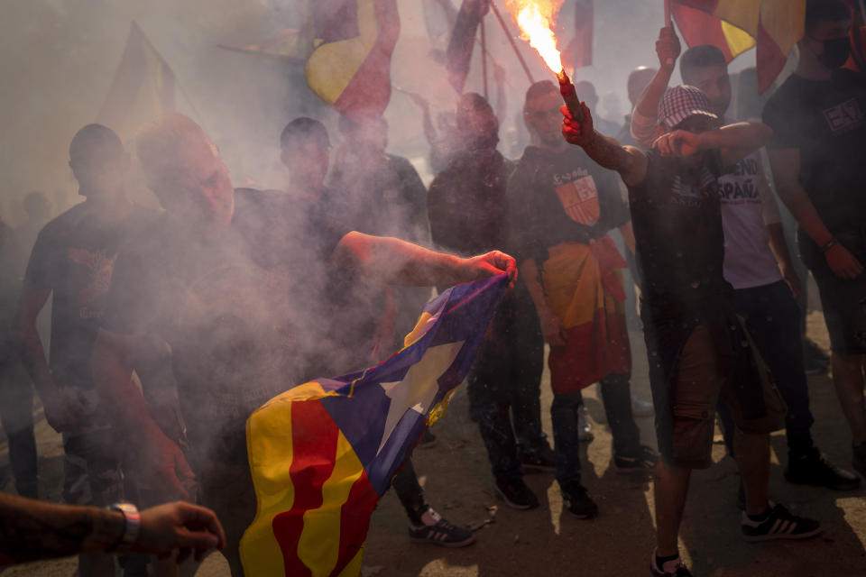 """Ultra right wing protesters burn """"esteladas"""" or Catalonia independence flags as they gather during an alternative celebration for Spain's National Day in Barcelona, Spain, Tuesday, Oct. 12, 2021. Spain commemorates Christopher Columbus' arrival in the New World and also Spain's armed forces day. (AP Photo/Emilio Morenatti)"""
