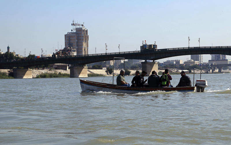 People cross the Tigris River in central Baghdad, Iraq, Tuesday, Nov. 19, 2019. Anti-government protests have effectively cut Iraq's capital in half and citizens are increasingly relying on boats to ferry them to the other side of the river city, as standoffs between demonstrators and security forces have shut three key bridges connecting east and west Baghdad. (AP Photo/Hadi Mizban)