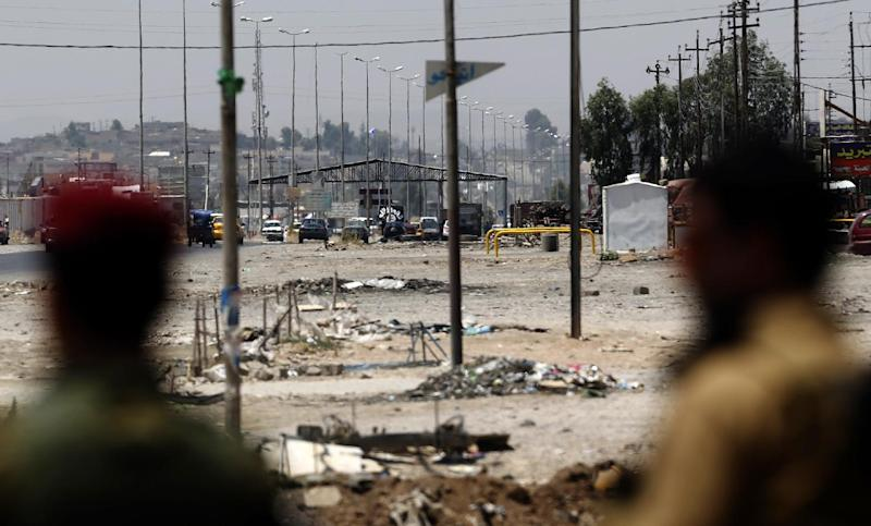 Kurdish Peshmerga forces look at a checkpoint held by militants of the Islamic State of Iraq and the Levant jihadist group on June 16, 2014 in Iraq's second city of Mosul