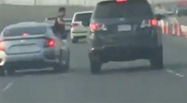 The passenger appears out of the window and starts punching at the other driver. Source: LiveLeak