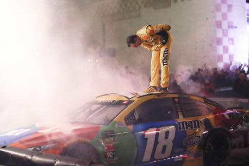 NASCAR driver Kyle Busch stands on his car and bows after competing in the Burnouts on Broadway competition Wednesday, Dec. 4, 2019, during NASCAR Champion's Week in Nashville, Tenn. (AP Photo/Mark Humphrey)