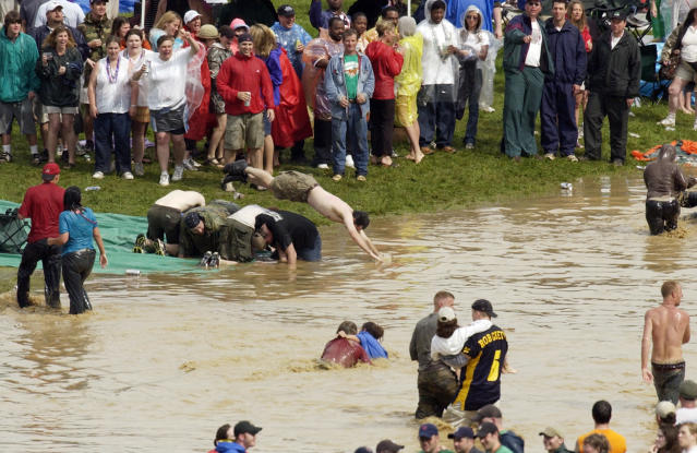 Revelers dive into a catch basin for rain water in the infield at Churchill Downs after a sudden downpour soaked the track during Kentucky Derby day festivities, Saturday, May 1, 2004, in Louisville, Ky. (AP)