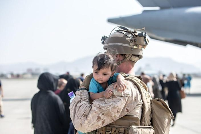 A Marine with Special Purpose Marine Air-Ground Task Force-Crisis Response-Central Command (SPMAGTF-CR-CC) calms an infant during an evacuation at Hamid Karzai International Airport, Kabul, Afghanistan, Aug. 21