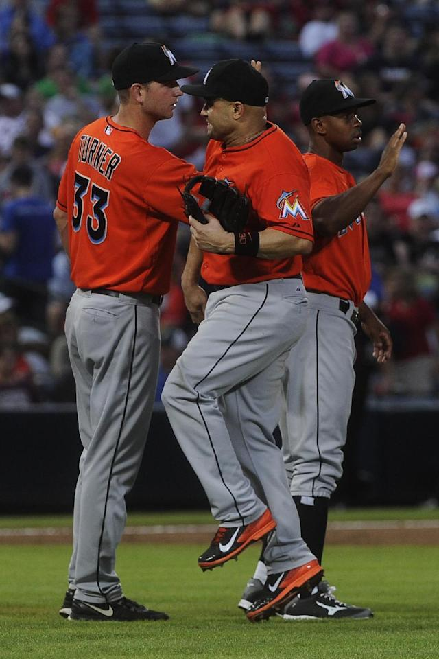 Miami Marlins third baseman Placido Polanco celebrates with teammate Jacob Turner (33) after a baseball game on Sunday, Sept. 1, 2013, in Atlanta. Miami won 7-0. (AP Photo/John Amis)