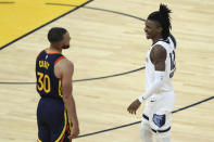 Memphis Grizzlies' Ja Morant, right, smiles after a foul was called against Golden State Warriors' Stephen Curry (30) during the second half of an NBA basketball Western Conference play-in game in San Francisco, Friday, May 21, 2021. (AP Photo/Jed Jacobsohn)