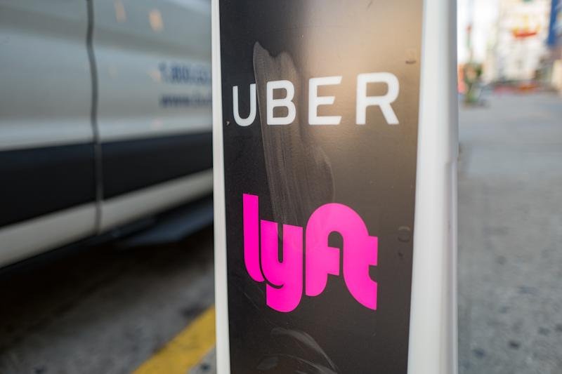 Close-up of vertical sign with logos for ridesharing companies Uber and Lyft, with wheels of a car in the background, indicating a location where rideshare pickups are available in downtown Los Angeles, California, October 24, 2018. (Photo by Smith Collection/Gado/Getty Images)